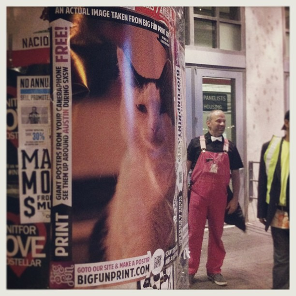 { #SXSW2013} The pink-overalls-clad gentleman had just taped on this big poster of a contemplative cat made with an app! ^ x ^  ビッグ・ポスターを作れるアプリ☆